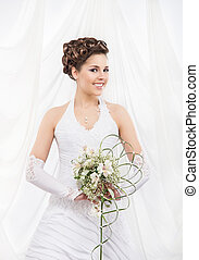 Young and beautiful bride standing with the flower bouquet...