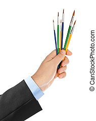 Hand with multicolored paintbrushes