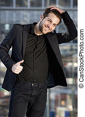 Male fashion model smiling with hand in hair - Portrait of a...
