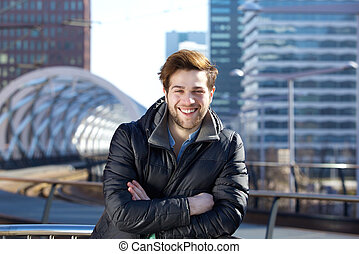 Happy young man standing downtown city - Close up portrait...