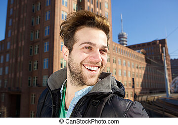 Cheerful young man walking in the city - Close up portrait...