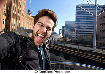 Selfie - Happy young man taking selfie in the city during...