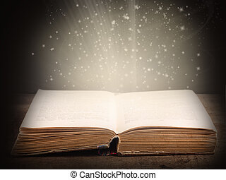 Old open book with magic light and falling stars on dark...