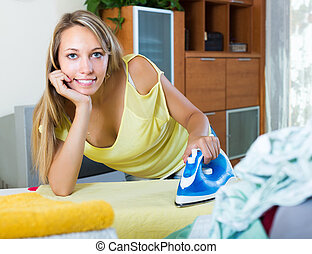 Blonde housewife ironing with iron - Smiling blonde young...