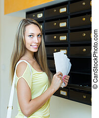 Young girl near posting box - Blonde girl taking junk mail...