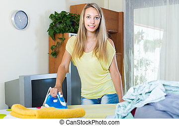 Blonde woman ironing at home - Smiling blonde long-haired...