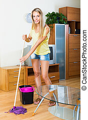 Woman washes the floor with mop