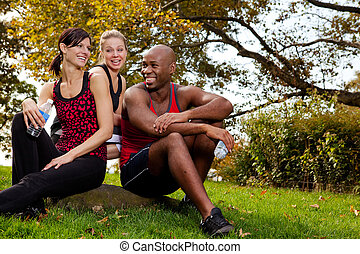 Exercise Group - A group of young adults resting after...
