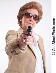 Female menace - Mature lady with sunglasses and a gun in her...