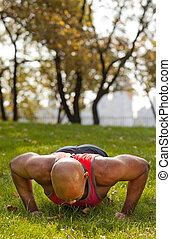 Exercise - An african american male doing push ups in a park