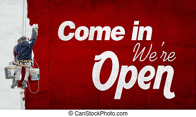 Come in, we are open - Painter hanging from building facade...
