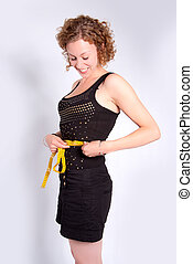 Successful diet - Fit young woman measuring her waste with a...