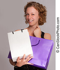 Satisfying shopping - Young blond woman happily holding two...