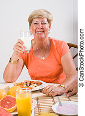 senior woman - a smiling senior woman having a glass of milk