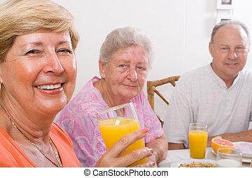 senior friends smiling together drinking orange juice