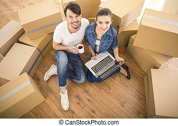 Moving home - The young happy couple searching for...