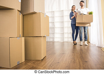 Moving home - The young happy couple looking around their...