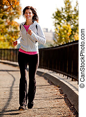 Jogging - A young woman jogging on a path in a park