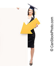 Young, beautiful and happy graduate girl pointing on a blank...