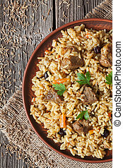 Pilaf traditional spicy asian food with rise, meat, onion,...