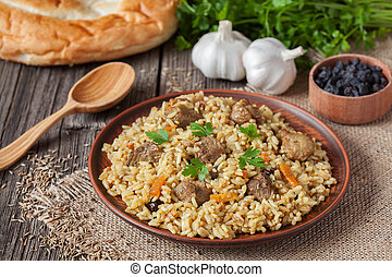 Traditional uzbek meal pilaf. Rice with meat, carrot and...