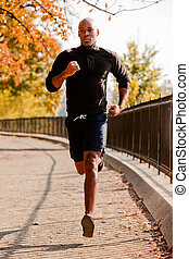 Running - An African American jogging in a park in the...