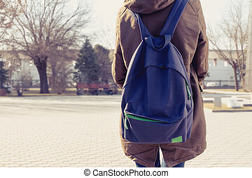 Rear view of hipster girl carring backpack on her back,...