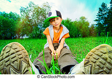 footwear - Teenager boy sitting on a grass at a park. Summer...