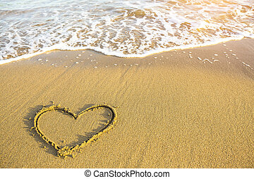 Heart drawn on the sand of a Sea beach, soft wave in a sunny day.
