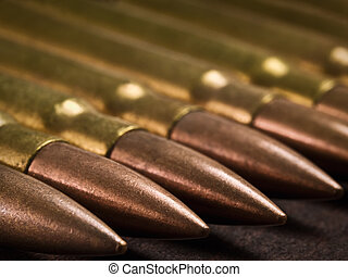 munition closeup - bullets in a row on the wooden surface,...