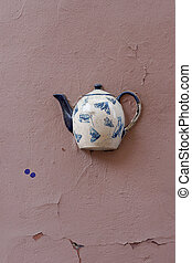 Old teapot on wall in Vilnius - Old teapot with insects...