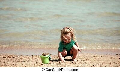 Baby girl playing bucket and shovel dig on sand beach sea