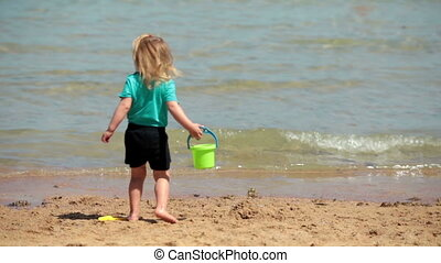 Baby girl playing bucket and shovel dig on sand beach sea -...