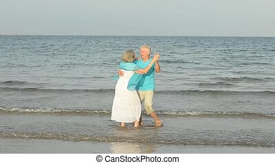 Elderly couple dancing on the beach - Beautiful elderly...