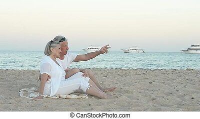 elderly couple sitting on a beach