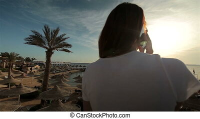 Young woman talking phone in sunset or sunrise resort on sea...