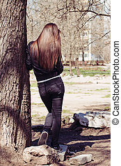 Young woman leaning on the old big tree