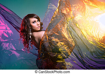 Young attractive model posing with the blowing silk