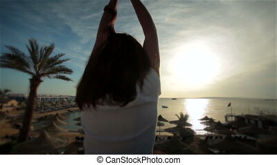 Young beautiful happy girl relax in sun seashore sunset or...