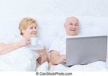 Couple interacts in bed - Socializing in bed. Elderly female...