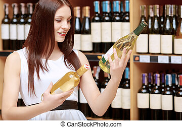 Woman holds a wine bottle in the store - Making choice Young...