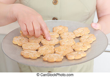 Woman holds a plate with biscuits - Home-made tasty...