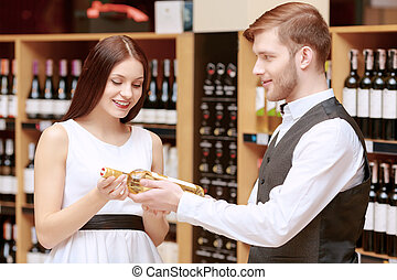 Woman interacts with a sommelier in shop