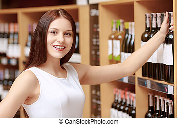 Woman buys wine in a store