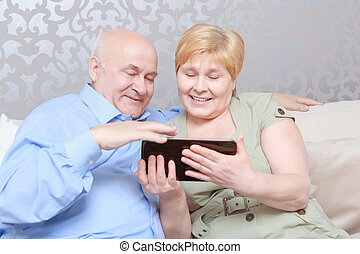 Couple reads a book at home - Social networking for all...