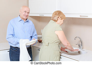 Couple washes dishes in the kitchen