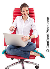 Happy woman with PC on red chair
