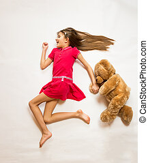 conceptual shot of cute happy girl running with teddy bear -...