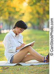 young beautiful asian woman writing text in diary book in...