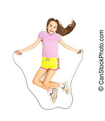 Isolated shot of cute active girl jumping with skipping rope...